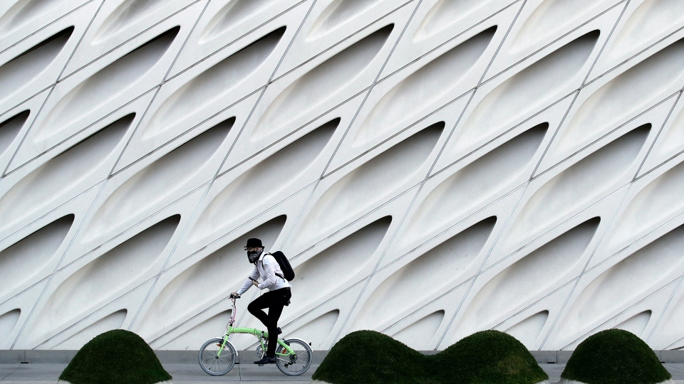William Iwneferi wears a mask as he rides past The Broad Museum on Wednesday, April 1, 2020, in Los Angeles. Los Angeles Mayor Eric Garcetti has recommended that the city's 4 million people wear masks when going outside amid the spreading coronavirus. (AP Photo/Marcio Jose Sanchez)