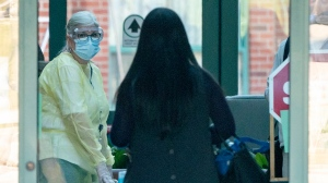 A nurse in protective gear greets a woman entering the Seven Oaks Long-Term Care Home in Toronto on Thursday, April 2, 2020. A number of residents at the home have died from COVID-19. THE CANADIAN PRESS/Frank Gunn