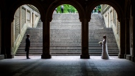 In this Tuesday, May 23, 2017 file photo, a bride and groom pose for wedding pictures at the Bethesda Terrace in New York's Central Park.  (AP Photo/Mary Altaffer)