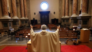 Don Angelo Riva celebrates a mass in an empty church after Italy's lockdown measure to prevent the spread of Covid-19, in Carenno, Italy, Thursday, April 2, 2020. The new coronavirus causes mild or moderate symptoms for most people, but for some, especially older adults and people with existing health problems, it can cause more severe illness or death. (AP Photo/Antonio Calanni)