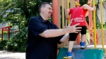 In this Monday, June 4, 2018, file photo, Glen Wood, a Canadian who has lived in Japan for 30 years, plays with his son at a Tokyo park. A Japanese court has rejected the demand by former brokerage manager Wood to get his job back after he took paternity leave at Mitsubishi UFJ Morgan Stanley. (AP Photo/Yuri Kageyama, File)