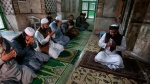 Unmasked worshippers offer Friday prayers at a mosque during a lockdown to to help stop the spread of the coronavirus in Peshawar, Pakistan, March, 3, 2020. Some mosques were allowed to remain open in Pakistan on Friday, the Muslim sabbath when adherents gather for weekly prayers, even as the coronavirus pandemic spread and much of the country had shut down. (AP Photo/Muhammad Sajjad)