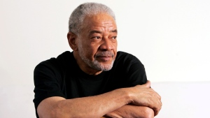 "FILE - In this June 21, 2006 file photo, singer-songwriter Bill Withers poses in his office in Beverly Hills, Calif. Withers, who wrote and sang a string of soulful songs in the 1970s that have stood the test of time, including ""Lean On Me,"" ""Lovely Day"" and ""Ain't No Sunshine,"" died in Los Angeles from heart complications on Monday, March 30, 2020. He was 81. (AP Photo/Reed Saxon, File)"