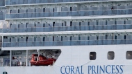 People look out from the Coral Princess cruise ship as it is docked at PortMiami during the new coronavirus outbreak, Saturday, April 4, 2020, in Miami. According to Princess Cruises, disembarkation of guests is expected to take several days due to limited flight availability. Guests requiring shoreside medical care will be prioritized to disembark first. (AP Photo/Lynne Sladky)