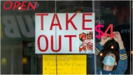 A man tapes signs in a restaurant window in Toronto on Sunday March 22, 2020. THE CANADIAN PRESS/Frank Gunn