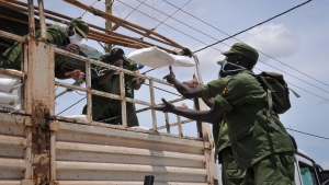 Members of the country's armed forces, the Uganda People's Defence Force (UPDF), help to distribute foodstuffs to people affected by the lockdown measures aimed at curbing the spread of the new coronavirus, in the Bwaise suburb of the capital Kampala, Uganda Saturday, April 4, 2020. Officials on Saturday started distributing food, mostly maize meal, beans and salt, plus milk powder for pregnant women, targeting 1.5 million vulnerable people, most of them slum dwellers, living in the metropolitan area encompassing the capital, which is under lockdown. (AP Photo/Ronald Kabuubi)