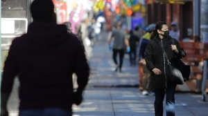 A woman wearing a mask walks on Roosevelt Avenue Saturday, April 4, 2020, in the Queens borough of New York. The new coronavirus causes mild or moderate symptoms for most people, but for some, especially older adults and people with existing health problems, it can cause more severe illness or death. (AP Photo/Frank Franklin II)