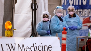 In this March 17, 2020, file photo, medical personnel wait for a driver to pull up at a drive-thru COVID-19 testing station for University of Washington Medicine patients in Seattle. Experts and health officials who are trying to plan a response to the coronavirus outbreak are missing a critical piece of information – the number of health care workers who have tested positive for the disease. (AP Photo/Elaine Thompson, File)