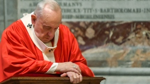 Pope Francis prays as he celebrates Palm Sunday Mass behind closed doors in St. Peter's Basilica, at the Vatican, Sunday, April 5, 2020, during the lockdown aimed at curbing the spread of the COVID-19 infection, caused by the novel coronavirus. (AP Photo/pool/Alberto Pizzoli)