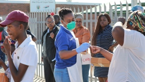In this photo taken Thursday, April 2, 2020 medical workers prepare to test people for COVID-19 at a testing clinic in Khayelitsha, Cape Town, South Africa. South Africa, one of the world's most unequal countries with a large population vulnerable to the new coronavirus, may have an advantage in the coronavirus outbreak, honed during years battling HIV and tuberculosis: the know-how and infrastructure to conduct mass testing. (AP Photo/Nardus Engelbrecht)