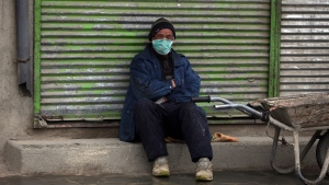 A day laborer wears a protective face mask to help curb the spread of the coronavirus as he waits for customers in Kabul, Afghanistan, Monday, April 6, 2020. (AP Photo/Rahmat Gul)