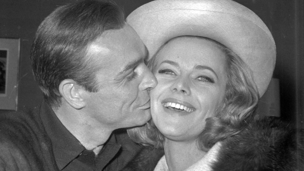 In this B/W file photo dated March 25, 1964, British actor Sean Connery kisses actress Honor Blackman during a party at Pinewood Film Studios, in Iver Heath, England. (AP Photo, FILE)