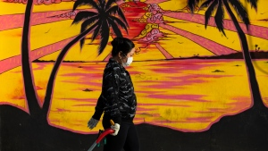 A woman walks past graffiti as she wears a protective face mask and gloves amid concerns over the country's coronavirus outbreak, in Tel Aviv, Israel, Monday, April 6, 2020. (AP Photo/Oded Balilty)