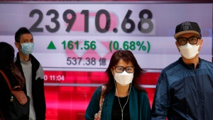 People wearing face masks walk past an electronic board showing Hong Kong share index outside a local bank in Hong Kong, Tuesday, April 7, 2020. Asian shares are rising, echoing the rally on Wall Street fueled by signs of hope that the coronavirus pandemic could be slowing. (AP Photo/Kin Cheung)