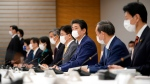 Japanese Prime Minister Shinzo Abe, center, declares a state of emergency during a meeting of the task force against the coronavirus at the his official residence in Tokyo, Tuesday, April 7, 2020. Abe declared a state of emergency for Tokyo and six other prefectures to ramp up defenses against the spread of the coronavirus. (Franck Robichon/Pool Photo via AP)