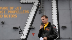 In this Nov. 15, 2019, photo U.S. Navy Capt. Brett Crozier, commanding officer of the aircraft carrier USS Theodore Roosevelt (CVN 71), addresses the crew during an all-hands call on the ship's flight deck while conducting routine operations in the Eastern Pacific Ocean. U.S. defense leaders are backing the Navy's decision to fire the ship captain who sought help for his coronavirus-stricken aircraft carrier, even as videos showed his sailors cheering him as he walked off the vessel. Videos went viral on social media Friday, April 3, 2020, showing hundreds of sailors gathered on the ship chanting and applauding Navy Capt. Brett Crozier as he walked down the ramp, turned, saluted, waved and got into a waiting car. (U.S. Navy Photo by Mass Communication Specialist 3rd Class Nicholas Huynh via AP)
