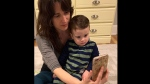 This March 30, 2020, photo taken on a self timer provided by Melissa Biddle shows herself with her 20-month-old son as they talk on the phone with the boy's father in Delaware County, Pa. The coronavirus is wreaking havoc on divorced families' custody arrangements as parents get sick or exposed to the illness. Biddle said she's caring full-time for her son because her ex-husband has been working to repair heating and air systems in grocery stores, and they both agreed this carried too much risk. (Melissa Biddle via AP)