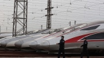 In this April 6, 2020, photo released by Xinhua News Agency, Chinese police officers wearing masks against new coronavirus walk past high speed trains parked a depot in Wuhan, in central China's Hubei Province. The central Chinese city of Wuhan, once the epicenter of the novel coronavirus outbreak, will resume outbound operation of passenger trains departing starting April 8, according to the local railway operator. (Zhao Jun//Xinhua via AP)