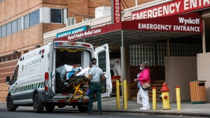 Patients are brought into Wyckoff Heights Medical Center by staff wearing personal protective gear due to COVID-19 concerns, Tuesday, April 7, 2020, in the Brooklyn borough of New York. The new coronavirus causes mild or moderate symptoms for most people, but for some, especially older adults and people with existing health problems, it can cause more severe illness or death. (AP Photo/John Minchillo)