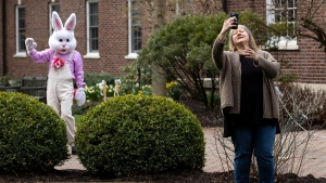 Lisa Farrell of Dalton, Pa. takes a selfie with the Easter Bunny from a safe social distance outside the Waverly Community House in Waverly Twp., Pa. on Saturday, April 4, 2020. (Christopher Dolan/The Times-Tribune via AP)
