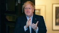 In this Thursday, April 2, 2020 handout photo provided by 10 Downing Street, Britain's Prime Minister Boris Johnson claps outside 11 Downing Street to salute local heroes during Thursday's nationwide Clap for Carers NHS initiative to applaud workers fighting the coronavirus pandemic, in London. Johnson has been moved to the intensive care unit of a London hospital on Monday, April 6, 2020 after his coronavirus symptoms worsened. Johnson's office says Johnson is conscious and does not require ventilation at the moment. Johnson was admitted to St. Thomas' Hospital late Sunday, 10 days after he was diagnosed with COVID-19. (Pippa Fowles/10 Downing Street via AP, File)
