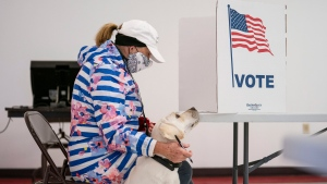 Catherine Anderson sits with her dog, Ivy, as she votes in the Wisconsin Primary at the Billings Park Civic Center in Superior, Minn., Tuesday, April 7, 2020. (Alex Kormann/Star Tribune via AP)