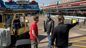 In this April 6, 2020, photo, Billy White, right, and his brother Sonny White, second from right, owners of Captain White Seafood City, along with their nephew Paul White, left, and Stan Kiser with Jessie Taylor Seafood, second from left, set up portable fencing in the hope to force customers to social distance at the Fish Market at The Wharf in Washington. The Fish Market was closed by city officials over the weekend after large crowds gathered. The officials said the market may be allowed to reopen if they can show a plan for safe social distancing. (AP Photo/Andrew Harnik)
