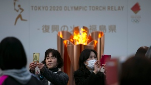 In this March 24, 2020, file photo, people take pictures with the Olympic Flame during a ceremony in Fukushima City, Japan. The Olympic flame has been removed from public display in Japan, and it's not clear when it will reappear again or where. The flame arrived in Japan from Greece on March 26. (AP Photo/Jae C. Hong, File