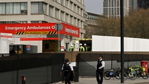Workers build a fence to block the view of the ambulance entrance area outside St Thomas' Hospital in central London, where Prime Minister Boris Johnson remains in intensive care as his coronavirus symptoms persist, Wednesday, April 8, 2020. Johnson has spent his second night in hospital intensive care. The new coronavirus causes mild or moderate symptoms for most people, but for some, especially older adults and people with existing health problems, it can cause more severe illness or death. (AP Photo/Matt Dunham)