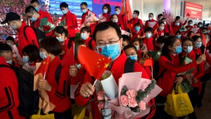 Medical workers from China's Jilin Province react as they prepare to return home at Wuhan Tianhe International Airport in Wuhan in central China's Hubei Province, Wednesday, April 8, 2020. (AP Photo/Ng Han Guan)