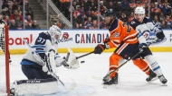 Winnipeg Jets goalie Connor Hellebuyck (37) makes the save on Edmonton Oilers' Darnell Nurse (25) as Jack Roslovic (28) defends during second period NHL action in Edmonton, Alta., on Wednesday March 11, 2020. THE CANADIAN PRESS/Jason Franson
