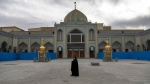 In this Saturday, March 7, 2020 photo, a woman with a mask walks in the yard of a Friday prayer mosque in Shahr-e-Ray, south of Tehran, Iran. The typically frenetic streets of Iran's capital, Tehran, have fallen silent and empty due to the new coronavirus outbreak that's gripped the Islamic Republic. (AP Photo/Ebrahim Noroozi)