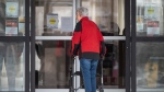A person re-enters a building at the Promenade retirement residence, where local health officials reported Ottawa's first case of COVID-19 in a retirement or long-term care home after a resident tested positive for the novel coronavirus, on Saturday, March 28, 2020. THE CANADIAN PRESS/Justin Tang