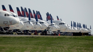 In this April 1, 2020, file photo, several dozen mothballed Delta Air Lines jets are parked at Kansas City International Airport in Kansas City, Mo. The number of Americans getting on airplanes has sunk to a level not seen in more than 60 years as people shelter in their homes to avoid catching or spreading the new coronavirus. The Transportation Security Administration screened fewer than 100,000 people on Tuesday, April 7, a drop of 95% from a year ago. (AP Photo/Charlie Riedel, File)