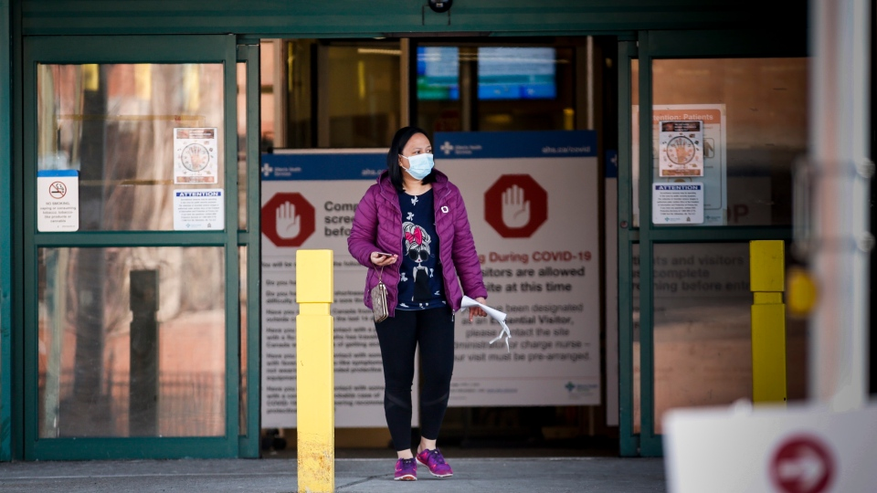 A woman leaves the Peter Lougheed Centre hospital in Calgary, Alta., Thursday, April 9, 2020, essential visitors are the only visitors permitted in Alberta hospitals as part of COVID-19 precautions. THE CANADIAN PRESS/Jeff McIntosh