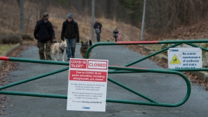 People walk their dogs along a path at High Park in Toronto on Tuesday, March 31, 2020. Ontario has closed recreation areas due to the coronavirus also known as COVID-19. THE CANADIAN PRESS/Nathan Denette