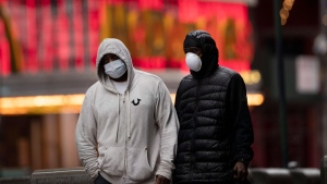 Men wearing masks walk through a rain storm in New York's Times Square, Thursday, April 9, 2020, during the coronavirus epidemic. (AP / Mark Lennihan)