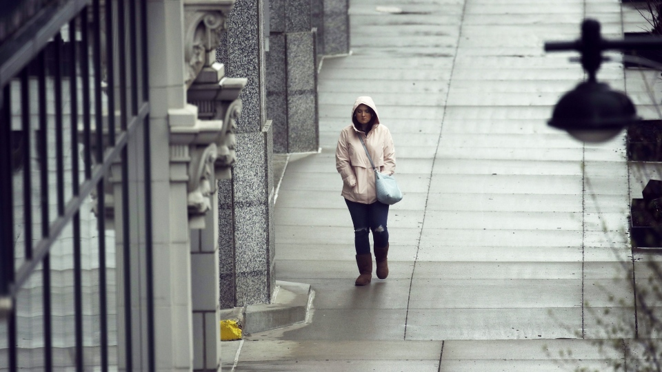 A person is seen walking down a sidewalk in this undated file photo. (The Canadian Press)