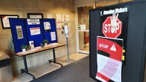 Warning signs and information about COVID-19 along with a hand sanitizing station is shown inside the doors of the Hillsdale Terraces Long-Term Care home in Oshawa, Ont., on Sunday, April 5, 2020. (THE CANADIAN PRESS/Doug Ives)