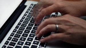 This June 19, 2017 file photo shows a person working on a laptop in North Andover, Mass. Many now are working and studying from home to limit the spread of the new coronavirus, one that's testing how productive people can be in a pandemic. It's also challenging the capacity of the internet, home Wi-Fi systems and video-chat services amid unprecedented demand. (AP Photo/Elise Amendola, File)