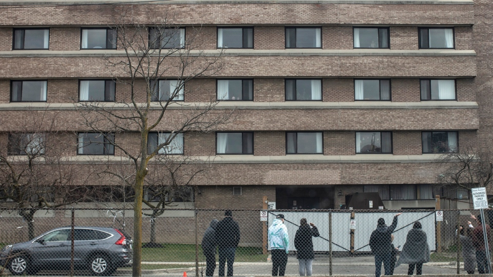 Family members wave to a relative as they stand outside the Eatonville Care Centre in Toronto on Saturday, April 18, 2020. THE CANADIAN PRESS/Chris Young