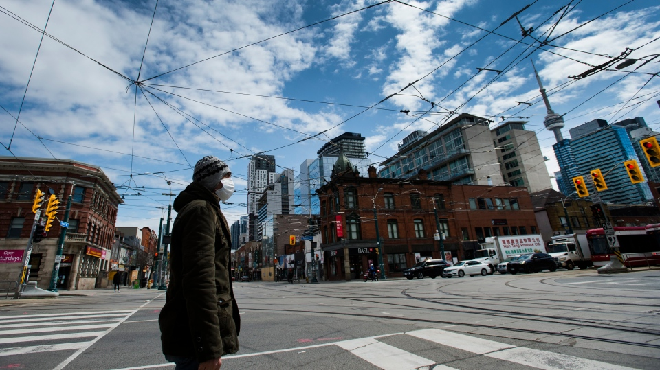 A lone man wears a mask while waiting at the intersection of Queen Street and Spadina Avenue in downtown Toronto on Thursday, April 16, 2020. Health officials and the government have asked that people stay inside to help curb the spread of COVID-19. THE CANADIAN PRESS/Nathan Denette