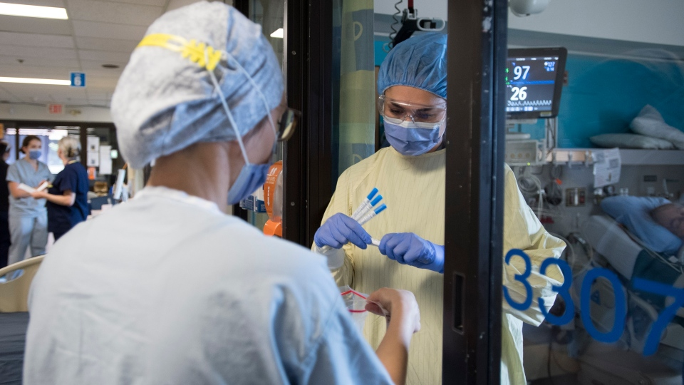 Nurses collect samples from a patient in a COVID suspect room in the COVID-19 intensive care unit at St. Paul's hospital in downtown Vancouver, Tuesday, April 21, 2020. THE CANADIAN PRESS/Jonathan Hayward