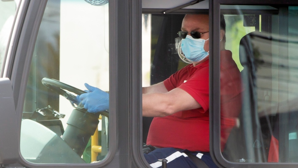 A Toronto Transit Commission bus driver wears a mask and gloves as he drives a bus in Toronto on Tuesday, April 14, 2020.THE CANADIAN PRESS/Frank Gunn