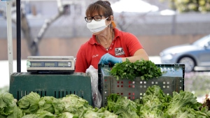 A worker wears a mask while selling produce at a farmers market amid the COVID-19 pandemic Wednesday, April 15, 2020, in Ventura, Calif. Canada's farmers markets, traditionally reliant on bustling crowds paying cash for locally produced food, seem particularly ill-suited to the age of physical distancing.THE CANADIAN PRESS/AP Photo/Marcio Jose Sanchez