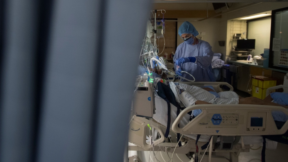 A nurse attends to a patient in a COVID positive room in a COVID-19 intensive care unit, Tuesday, April 21, 2020. THE CANADIAN PRESS/Jonathan Hayward
