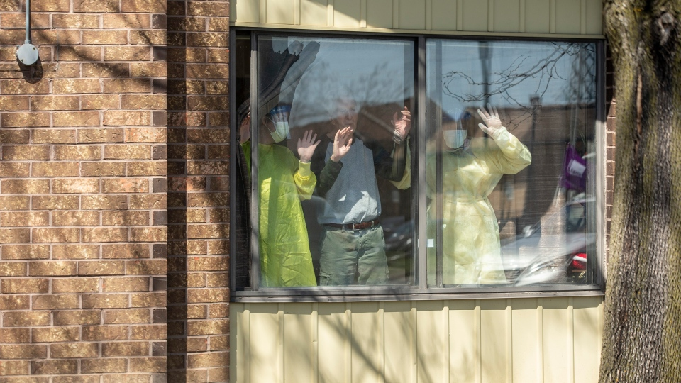 A resident stands with staff members as they watch well wishers drive through Orchard Villa Care home, in Pickering, Ont. on Saturday, April 25, 2020. THE CANADIAN PRESS/Chris Young