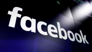 FILE - This March 29, 2018, file photo shows the Facebook logo on screens at the Nasdaq MarketSite in New York's Times Square. Facebook on Tuesday, April 28, 2020, reported its slowest quarterly growth as a public company, pressured by a global slowdown in the digital advertising market due to the coronavirus pandemic. (AP Photo/Richard Drew, File)