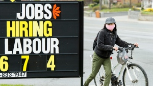 A woman checks out a jobs advertisement sign during the COVID-19 pandemic in Toronto on Wednesday, April 29, 2020. (THE CANADIAN PRESS / Nathan Denette)