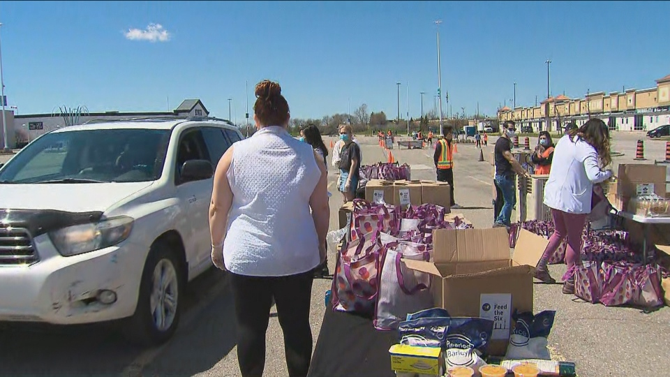 Volunteers hand out grocery care packages to drivers outside the Vaughan Mills shopping centre.